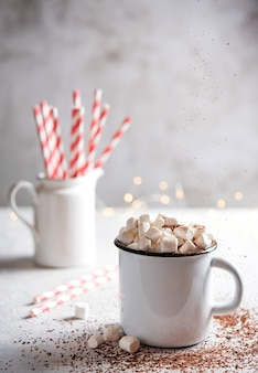 Hot chocolate with marshmallows and a red paper tube on a gray table. christmas photo. front and macro view