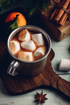 Hot chocolate with marshmallows on rustic cutting board