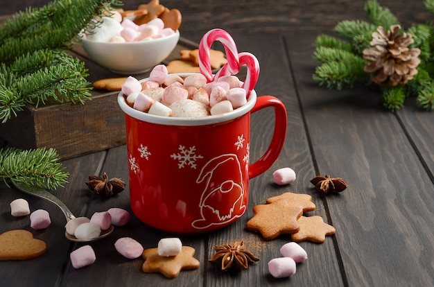 Hot chocolate with marshmallows and spices on dark wooden background. christmas compositio