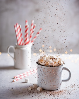 Hot chocolate with marshmallows, strew cacao and a red paper tube on a gray table