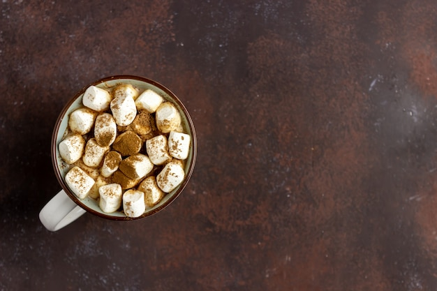 Hot chocolate with marshmallows in a white mug on a rusty background. winter. recipes.