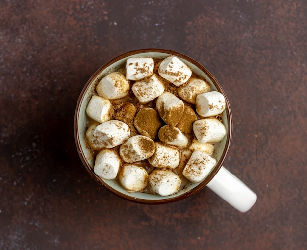 Hot chocolate with marshmallows in a white mug on a rusty