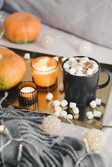 マシュマロが溶けたホットチョコレートは、カボチャのキャンドルとライトが付いた金属製のトレイを提供しました