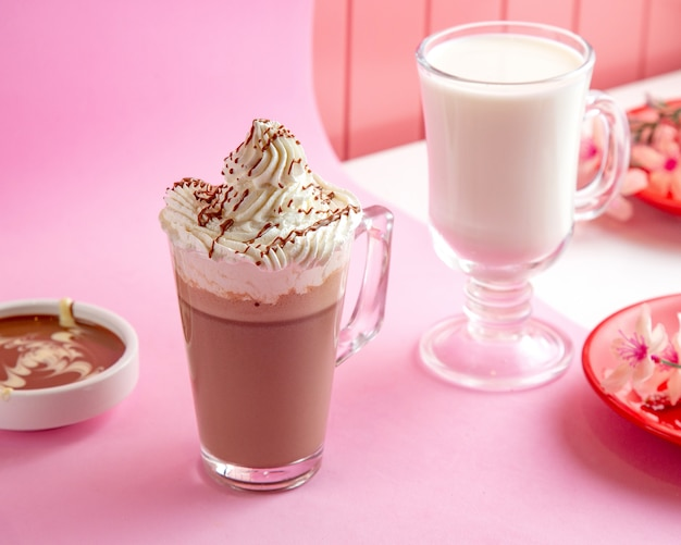 Hot chocolate with whipped cream milk and chocolate on table