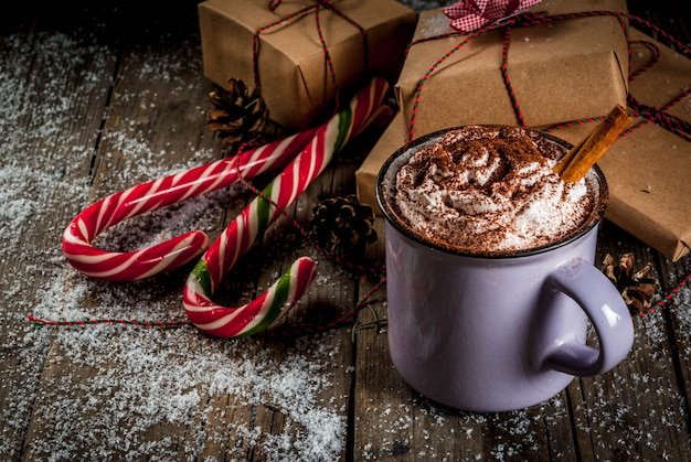 Hot chocolate with whipped cream and spices, christmas gifts and candy canes