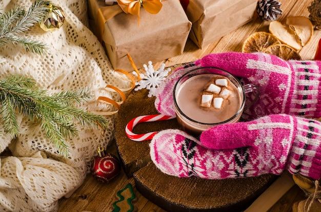 マシュマロとココアのホットクリスマスと新年の飲み物。ミトンの手は、贈り物やクリスマスツリーの枝と一緒にテーブルの上に飲み物とマグカップを持っています。ホットチョコレート。