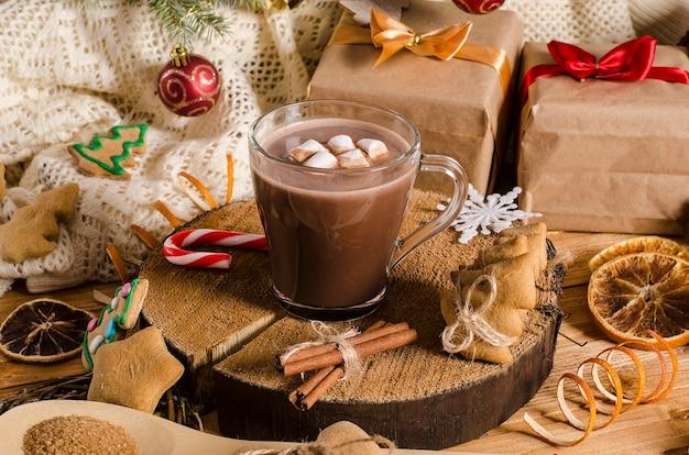 贈り物、クリスマスクッキー、クリスマスツリーの枝が付いているテーブルの上のマシュマロとココアの熱いクリスマスと新年の飲み物。ホットチョコレート。
