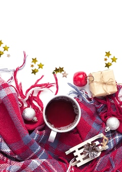 Hot christmas beverage black tea in mug with new year decorations, sledge, present, balls, plaid . winter time top view.