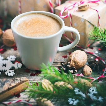 Hot christmas beverage in cup presents background