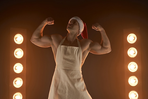 Hot christmas dessert sexy muscular chef wearing apron and santa hat show biceps smiling, lamps illumination and smoke on background cuisine. male housewife. husband in kitchen. brutal butcher.