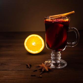 ホットクリスマスドリンクグリューワイン、スターアニス、シナモン、オレンジと木製のテーブル