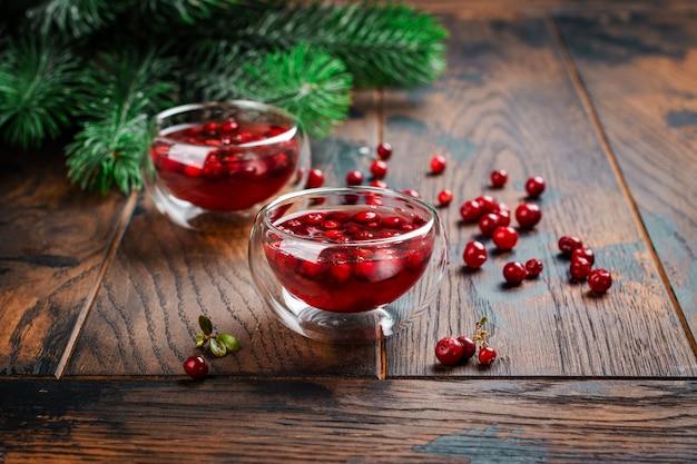 モミの木の枝が付いている木の上の熱いクリスマスまたは冬の酸っぱいクランベリー茶