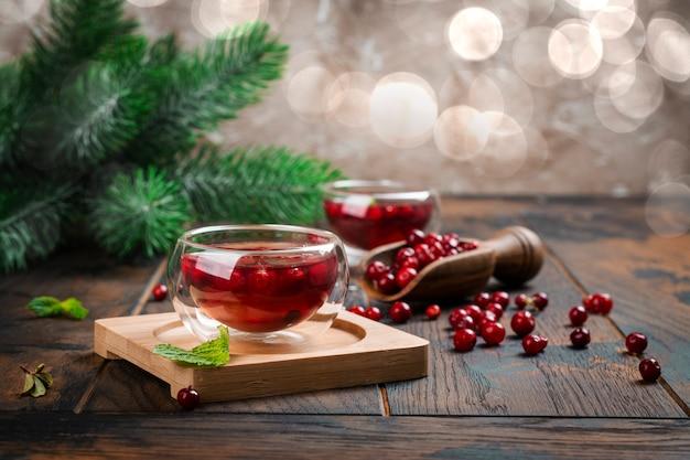 Горячий рождественский или зимний кислый клюквенный чай на деревянном