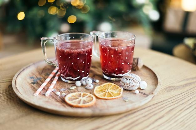 Горячий рождественский чай или глинтвейн на деревянном подносе с апельсиновым декором и новогодним декором у елки. праздничная атмосфера, уютное утро.