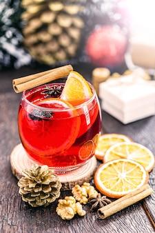 アニス、シナモン、柑橘系の果物を使ったホットクリスマスワイン。装飾とギフトを背景にした典型的な年末の飲み物
