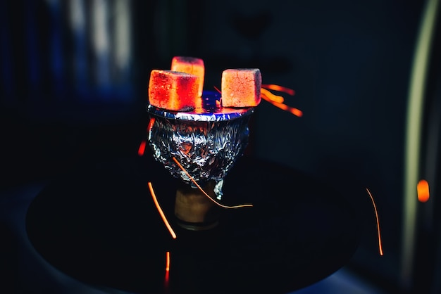 Hot coals on foil on bowl of hookah tobacco smoking