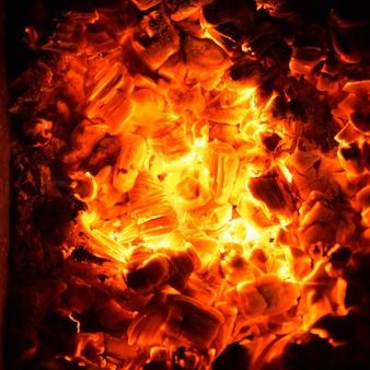 火の中の熱い石炭。燃えさしの抽象的な背景。