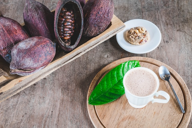 Hot cocoa and cocoa pod on wooden table