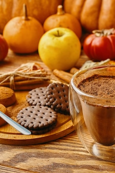 Hot cocoa cookies and autumn harvest on wooden table ripe pumpkins apples fall leaves and persimmons...