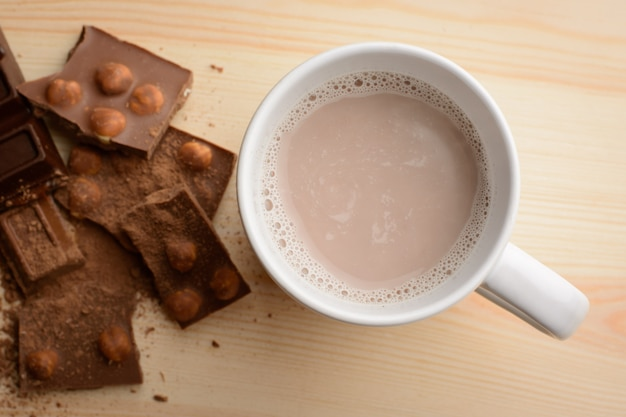Hot cocoa in cup near broken chocolate bar with hazelnuts on table