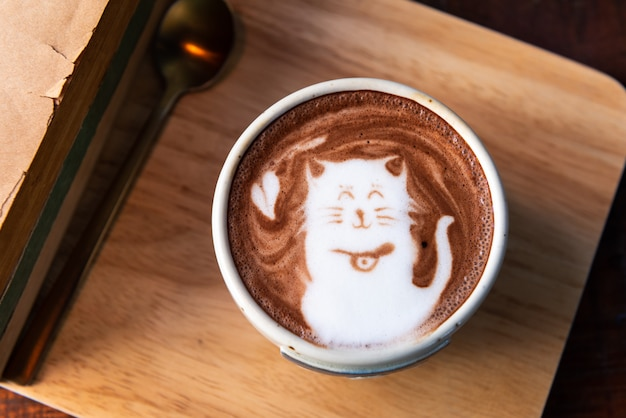 Hot cocoa cup topping cat shape with old books on wooden plate