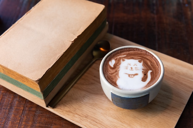 Hot cocoa cup with old books on wooden plate
