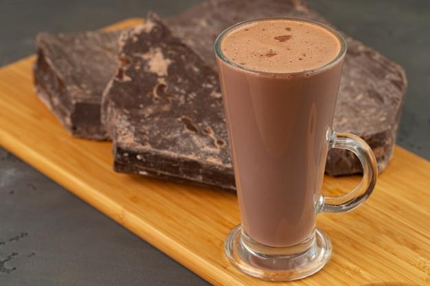 ガラスのカップと灰色の背景のチョコレートバーでホットココアドリンクをクローズアップ