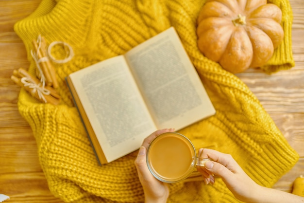 Hot cocoa in hands ripe pumpkin cinnamon sticks warm sweater and open book on wooden background vint...
