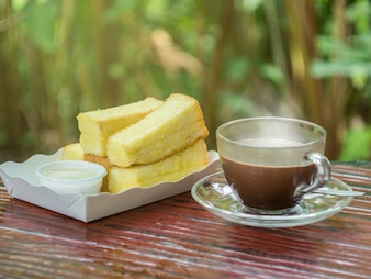 Hot cocoa in cup with bread baked with butter and condensed milk