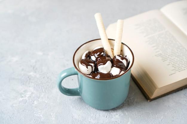 本の近くにマシュマロ、ワッフル、ホットチョコレートが入ったホットココアマグ。