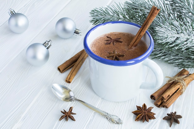 Горячее какао с корицей в металлической кружке на белом деревянном