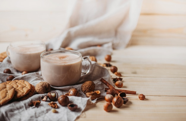 クッキー、シナモンスティック、アニス、木製のテーブル上のナッツと熱いココア。正面図、コピースペース。