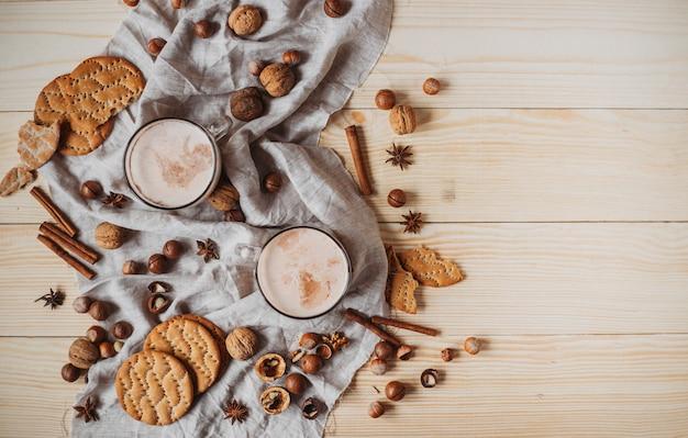 クッキー、シナモンスティック、アニス、木製のテーブル上のナッツとホットココア。正面図、コピースペース。