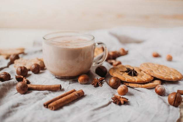 クッキー、シナモンスティック、アニス、木製のテーブル上のナッツと熱いココア。