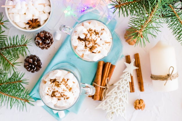 Hot cocoa with marshmallow and ground cinnamon in glasses in christmas decorations, top view