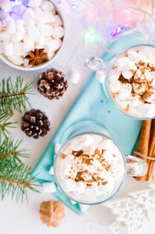 Hot cocoa with marshmallow and ground cinnamon in glasses on the table in christmas decorations, top view