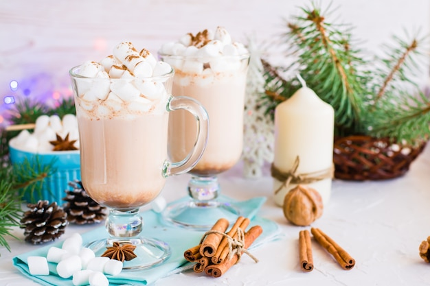 Hot cocoa with marshmallow and ground cinnamon in glasses on the table in christmas decorations