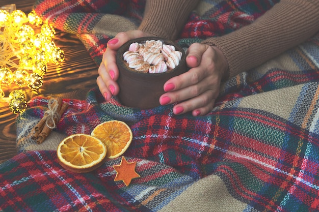 Hot cocoa with marshmallow in hand girl in knitted sweater, blanket and dry oranges with christmas lights. christmas, winter, new year concept. copy space,