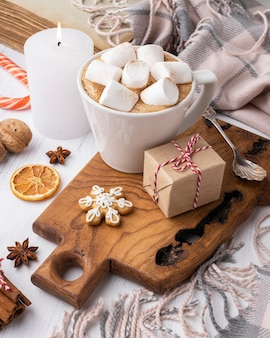 Hot cocoa with marshmallows in cup with present and candle