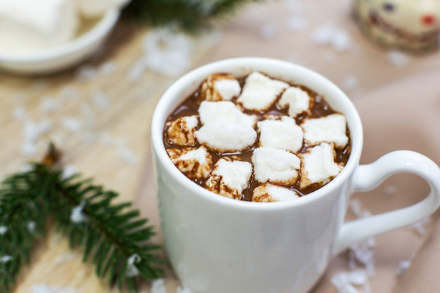 Hot cocoa with marshmallows in white mug, cream and cookies