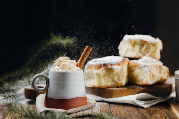 A hot cocoa with whipped cream, cinnamon stick and fresh christmas buns with powder and over festive table