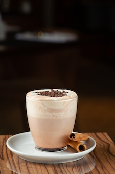 Hot cocoa on wooden table closeup with copy space on dark background.
