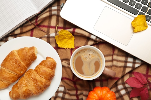 格子縞のノートとホットコーヒーと紅葉-季節のリラックスコンセプト。上面図