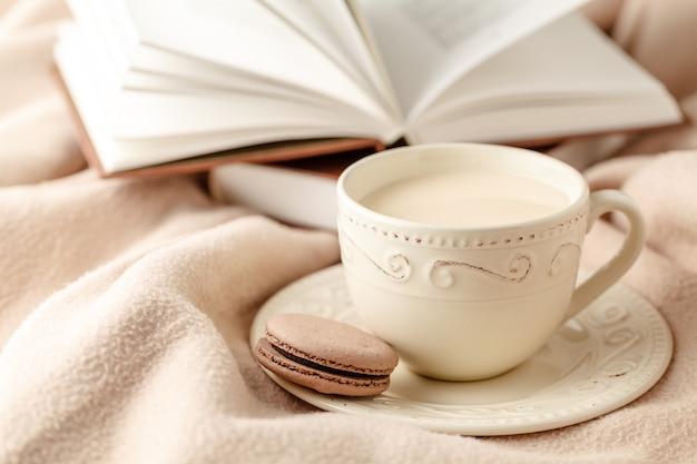 뜨거운 커피와 양모 배경에 책
