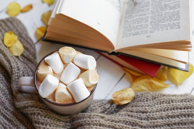 ホットコーヒーとウッドの背景に紅葉の本-季節のリラックスコンセプト