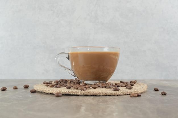 大理石のテーブルの上のホットコーヒーとコーヒー豆