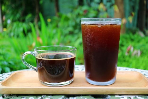 Горячий кофе и кофе со льдом на деревянном подносе, поданные на садовом столе