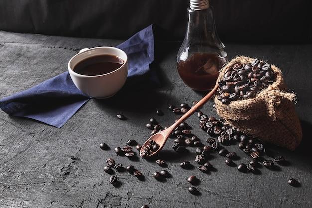 Горячий кофе и сырые кофейные зерна на черном фоне.