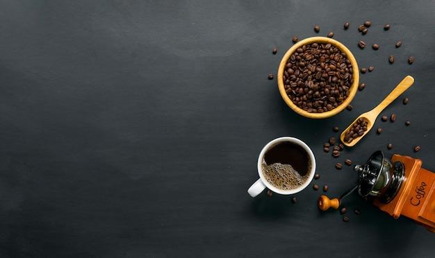 Горячий кофе, фасоль и ручная кофемолка на черном фоне стола. место для текста. вид сверху