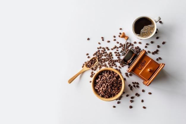 Горячий кофе, фасоль и ручная кофемолка на белом фоне таблицы. место для текста. вид сверху